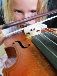 A small child has a go at playing a full-size violin.