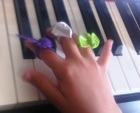 Young piano student plays with novelty rings on fingers